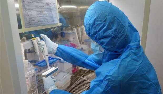A medical worker performs COVID-19 testing inside a mobile container lab in Vietnam. (Photo: VNA)