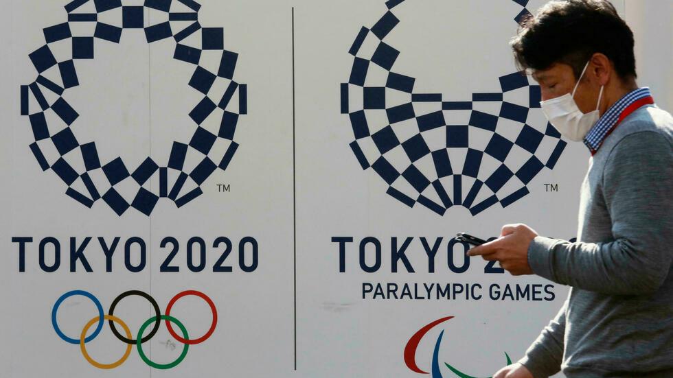 A man walks by logos of the Tokyo Olympic and Paralympic Games in Tokyo, Japan, February 1, 2021. © Koji Sasahara, AP