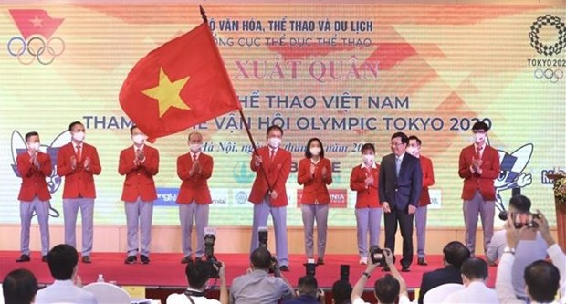 A member of the Vietnamese sports delegation holds the national flag handed over by Deputy Prime Minister Pham Binh Minh (front, right) at the send-off ceremony on July 13 (Photo: VNA)
