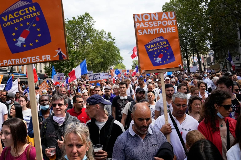 Protesters hold up signs that read 'no to the vaccine passport' during a demonstration in Paris [Michel Euler/AP]