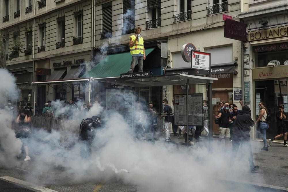 Protestors stand in smoke flares in front of policemen during a demonstration in Lyon, central France, Saturday, July 31, 2021. Demonstrators gathered in several cities in France on Saturday to protest against the COVID-19 pass, which grants vaccinated individuals greater ease of access to venues. (AP Photo/
