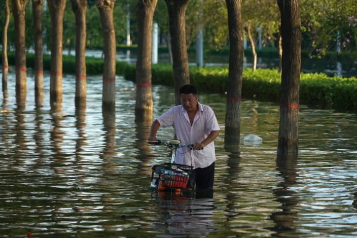 In this July 26, 2021, file photo, a man pushes a scooter through floodwaters in Xinxiang in central China's Henan Province, Monday, July 26, 2021. Chinese authorities have announced a huge jump in the death toll from recent floods. The Henan province government said Monday, Aug. 2, 2021, that over 300 have people died and at least 50 remain missing. (AP Photo/Dake Kang, File)