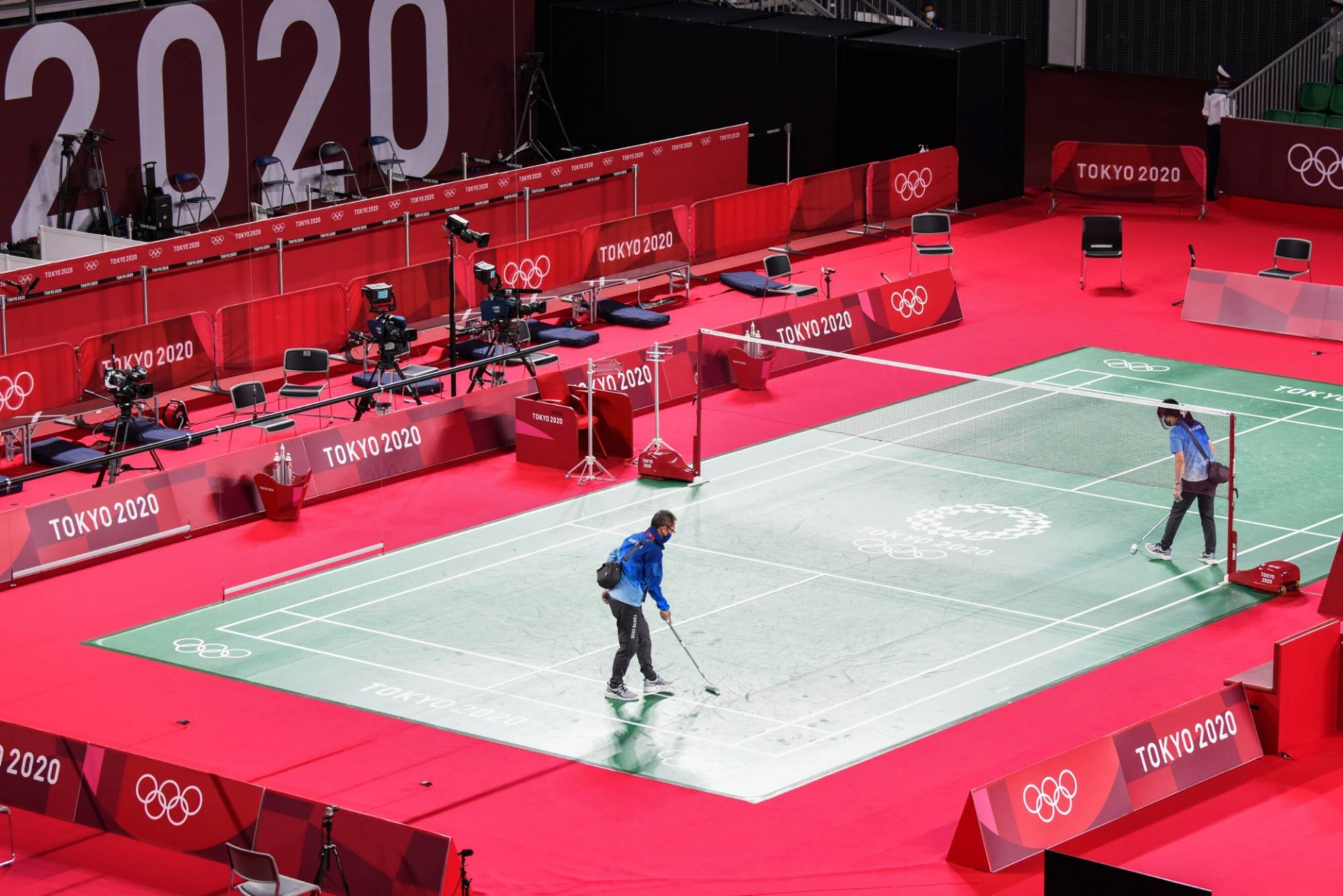 Volunteers clean up a court before badminton matches at the Musashino Forest Sport Plaza in Chofu, Tokyo.   BLOOMBERG