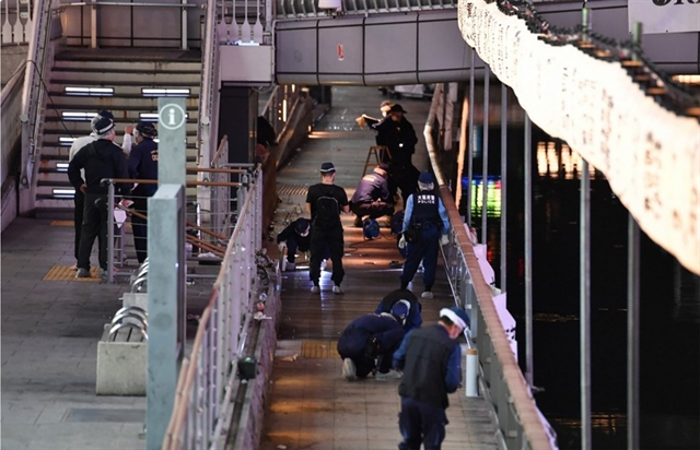 Police in Osaka, Japan examine a bridge in the Namba Parks area where a Vietnamese student was pushed into the Dotonbori River underneath and died on Monday. — Mainichi/VNA Photo