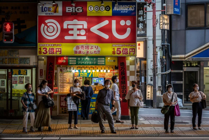 People wearing face masks wait to cross a street on July 28, 2021 in Tokyo, Japan. Tokyo metropolitan government reported 3,177 new coronavirus cases on Tuesday, an increase on yesterday and the highest number of infections recorded so far for the city. Yuichi Yamazaki—Getty Images
