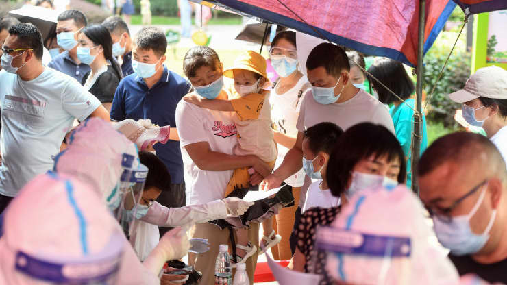 Residents of Wuhan city in China's Hubei province queue to take nucleic acid tests for Covid-19 on August 3, 2021. STR   AFP   Getty Images