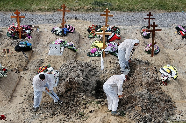 Gravediggers wearing personal protective equipment (PPE) as a preventive measure against the coronavirus disease (COVID-19) bury a body at a graveyard on the outskirts of Saint Petersburg, Russia June 25, 2021 [File: Anton Vaganov/Reuters]