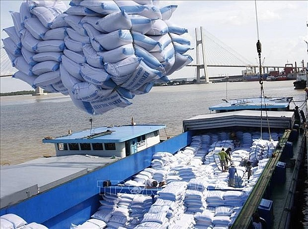 Loading and unloading rice for export at Saigon port.  (Source: VNA)