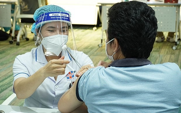 A medical worker gives COVID-19 vaccine shot to a man in HCM City. (Photo: VNA)