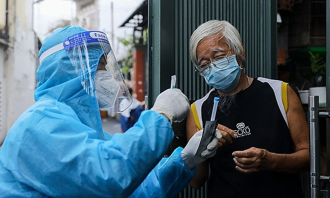 A medic guides a man in HCMC's Binh Thanh District to use a test kit on himself, August 23, 2021. Photo by VnExpress