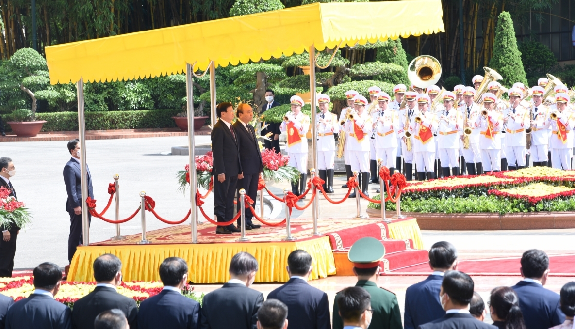 The Vietnamese State leader joins Laotian President Sisoulith at the speakers' podium as the national anthems of both countries are played.