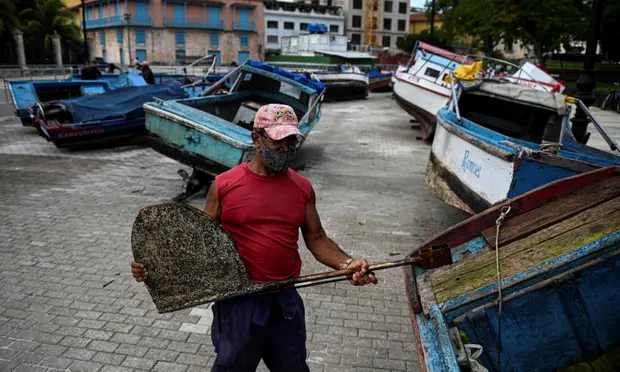 A fisherman secures his boat to land ahead of the passage of Tropical Storm Elsa in Havana. Photograph: Yamil Lage/AFP/Getty Images