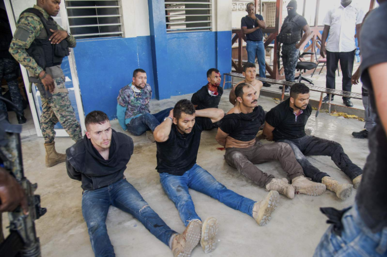 Suspects in the assassination of Haiti's President Jovenel Moise sit on the floor after being detained, at the General Direction of the police in Port-au-Prince, Haiti, Thursday, July 8, 2021. A Haitian judge involved in the murder investigation said that President Moise was shot a dozen times and that his office and bedroom were ransacked. (AP Photo/Jean Marc Herv Ablard) (Copyright 2021 The Associated Press. All rights reserved)