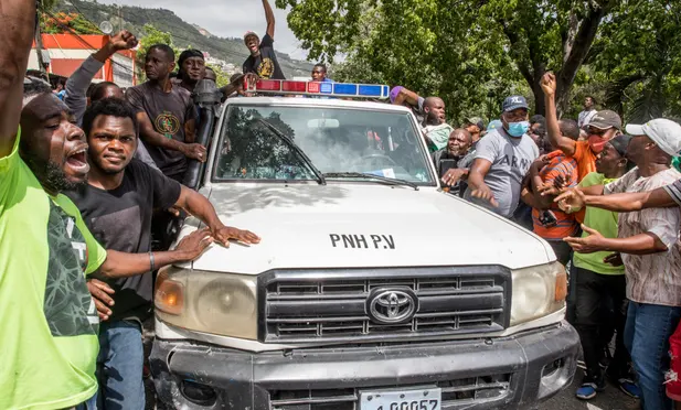People cheer as a police car drives past the police station where men, accused of being involved in the assassination of President Jovenel Moise, are being held in Port au Prince Photograph: AFP/Getty Images