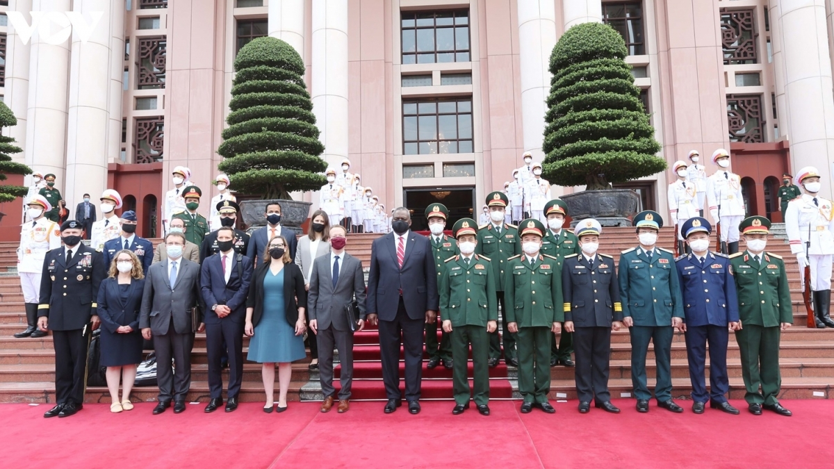 Minister Phan Van Giang and Secretary Lloy Austin (C) pose for a group photo in front of the Headquarters of the Defence Ministry in Hanoi.