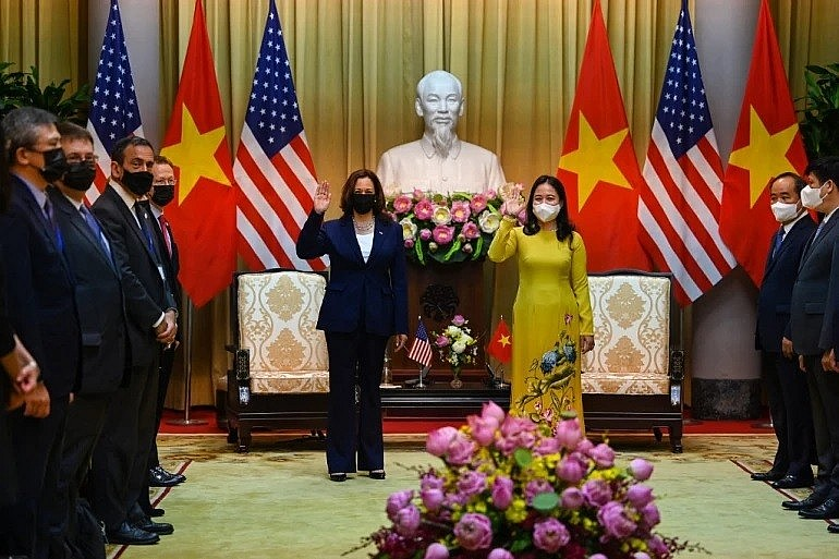US Vice President Kamala Harris (left) waves beside Vietnam's Vice President Vo Thi Anh Xuan at the Presidential Palace in Hano