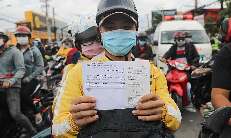A motorbike driver holds up his Covid-19 test result in Ho Chi Minh City, Oct. 1, 2021. Photo by VnExpress