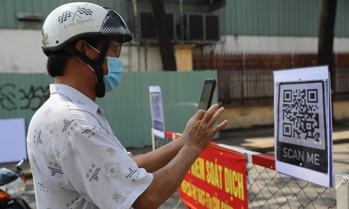 A man scans a QR code to complete the health declaration, one of the procedures everyone has to complete to get through Covid-19 checkpoints in Go Vap District, now the biggest Covid hotspot in HCMC, June 3, 2021. Photo: VnExpress