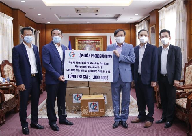 Chairman of Phongsubthavy Group Phongsavath Senaphuan (left) gives Ambassador Nguyen Ba Hung a check worth $500,000 to support Vietnam's Covid Prevention and Control Fund. Photo: VNA