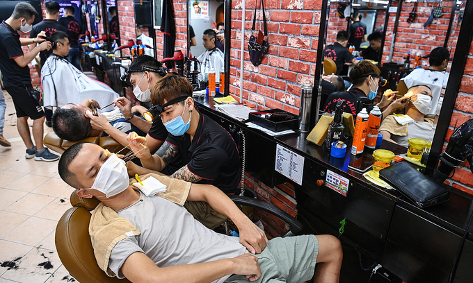 Customers at a barber shop on Hanoi's Dong Da District on May 25, 2021. Photo: VnExpress