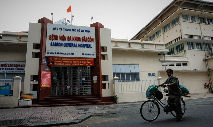 A man walks a bicycle past the Saigon General Hospital in HCMC's District, June 22, 2021. The hospital is currently locked down as linked to at least five Covid-19 cases. Photo: VnExpress