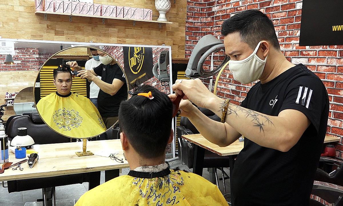 A customer has a haircut at a barbershop on Hanoi's Nguyen Hong Street on June 22, 2021. Photo: VnExpress
