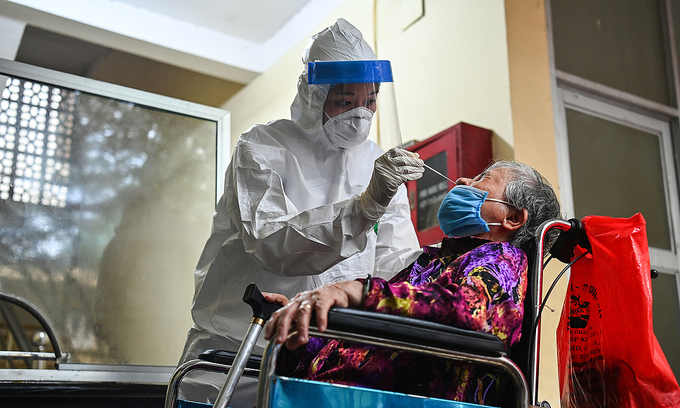 A medic takes the sample of a woman in Hanoi during a mass coronavirus test, May 2021. Photo by VnExpress/Giang Huy.