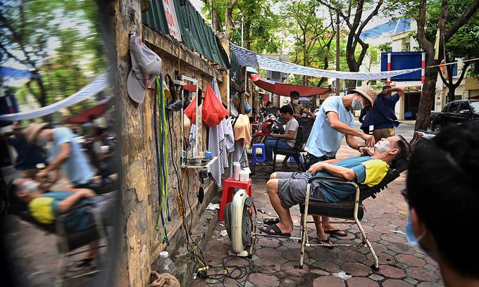 Barbers work on a sidewalk of Hanoi. Photo: VnExpress