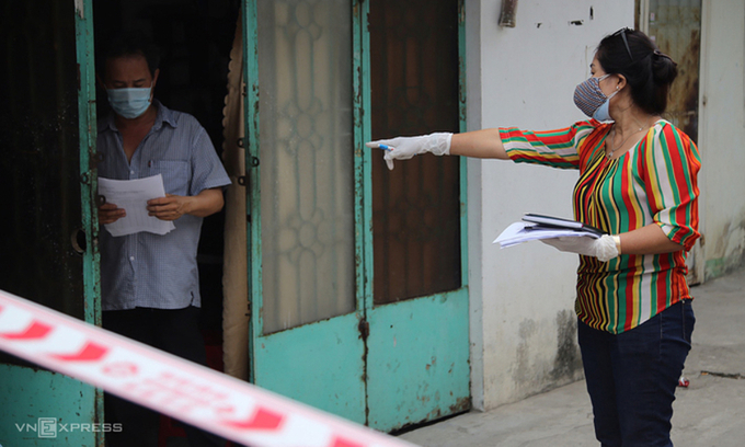 An official guides a man on protocols he should follow to quarantine himself at home in HCMC, February, 2021. Photo by VnExpress/Dinh Van.
