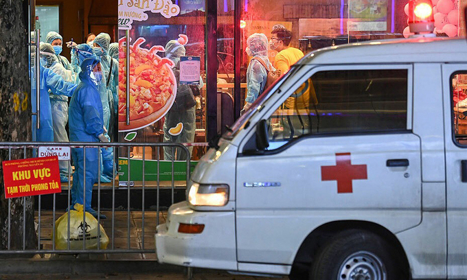 An ambulance and medical workers arrive at a pizza shop on Hanoi's Doan Tran Nghiep Street to lock it down due to Covid linkage, July 15, 2021. Photo: VnExpress
