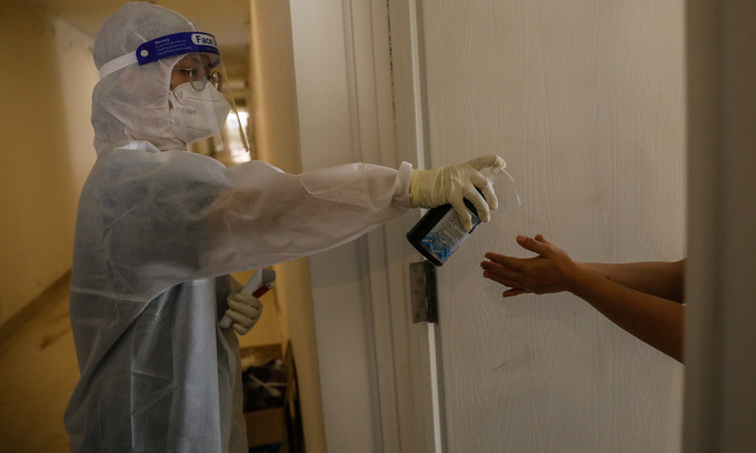 A doctor sprays disinfectant on a Covid-19 patient's hands inside a field hospital in HCMC's Thu Duc City, July 2021. Photo: VnExpress