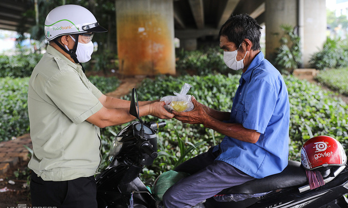 A motorbike taxi driver receives a charity meal in HCMC, July 2021. Photo: VnExpress