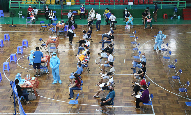 People wait for receiving Covid vaccine at a sports center in HCMC's District 11, July 22, 2021. Photo: VnExpress