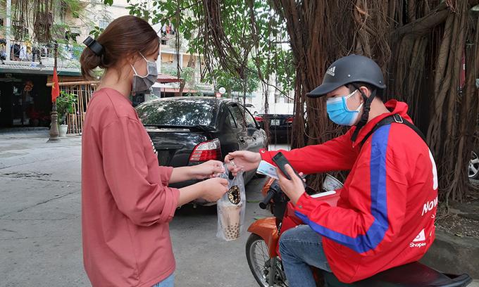 A shipper delivers a bubble milk tea order to a woman in Hanoi. Photo: VnExpress
