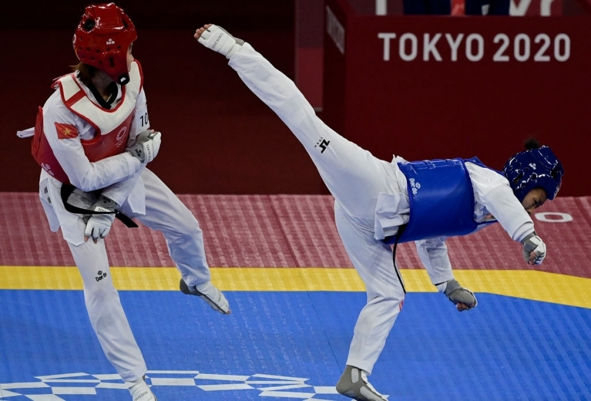 Kim Tuyen (in red gi) defeats Yvette Yong of Canada to enter the quarter-finals. Photo: Getty
