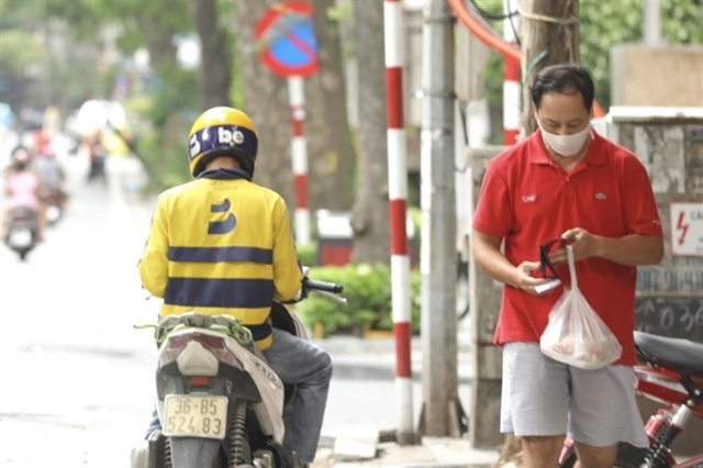 Delivery staff can work after registering with the Hà Nội Department of Transport and receive an allowance from the department. Photo: VNS
