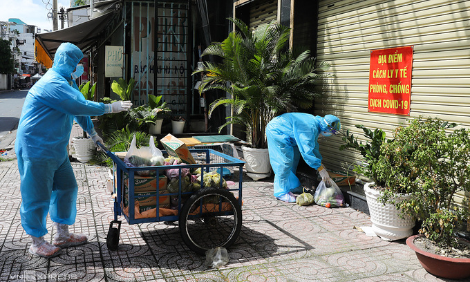 Volunteers distribute food to families under lockdown in HCMC's District 3, July 2021. Photo: VnExpress