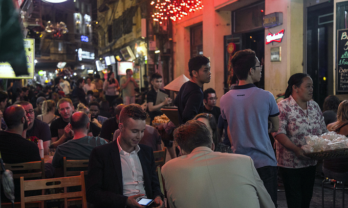 Foreign tourists sit at a beer stall in Ta Hien-Luong Ngoc Quyen intersection in Hanoi, 2019. Photo: VnExpress