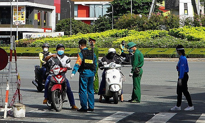 Forces check travel papers of people at a Covid checkpoint on Nguyen Binh Khiem Street in HCMC, August 23 2021. Photo: VnExpress