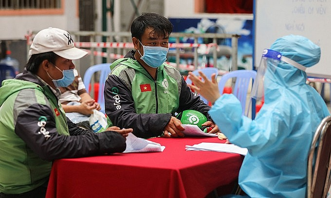 Shippers listen to a health worker at a Covid-19 vaccination point in HCMC's District 11, August 2, 2021. Photo: VnExpress