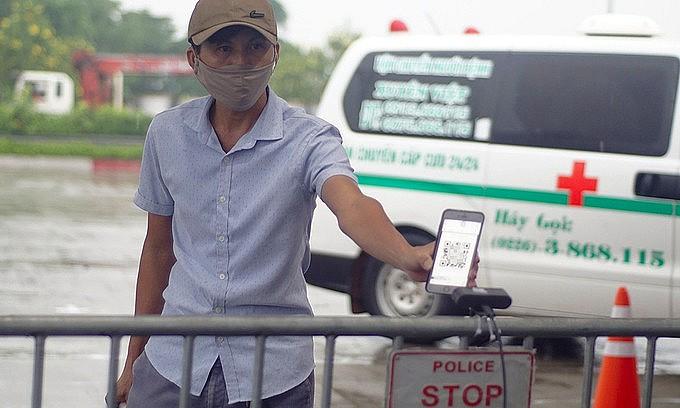 A man scans a QR code at a Covid-19 checkpoint to enter Hanoi, September 14, 2021. Photo: VnExpress