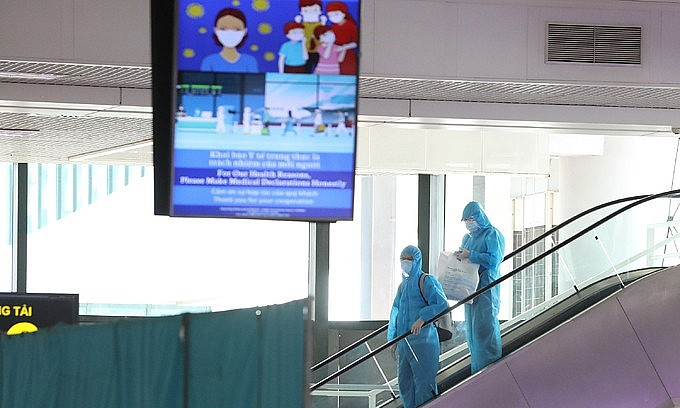 Two passengers wearing protective suits arrive at Hanoi's Noi Bai airport from HCMC, July 2021. Photo: VnExpress