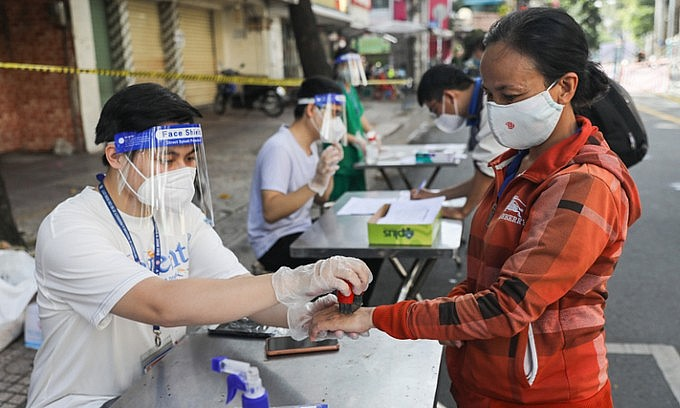 A medical staff stamps ink on the hand of a woman at a shopping location in District 5, Ho Chi Minh City, September 22, 2021. Photo: VnExpress