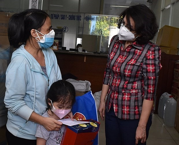 Local authorities present aid to an orphan who lost her parents to the COVID-19 pandemic in Ho Chi Minh City. Photo: VNA