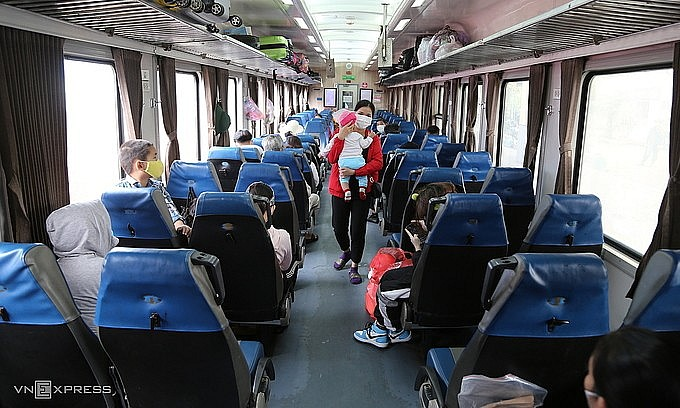 A woman carrying her baby on a train carrying migrant workers in HCMC home in central Vietnam, October 8, 2021. Photo: VnExpress